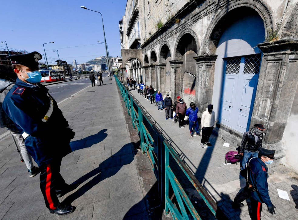 People line up outside a soup kitchen in Naples amid the coronavirus crisis
