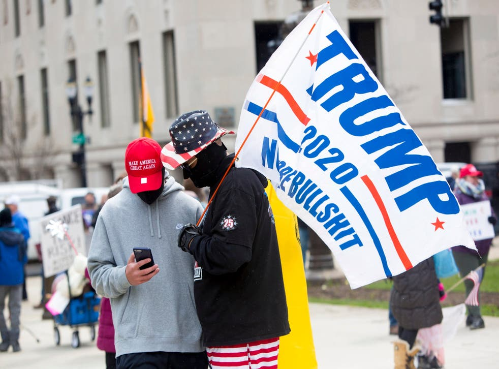 <p>Supporters wear MAGA hats and carry Trump flags at Michigan protest in 2020</p>