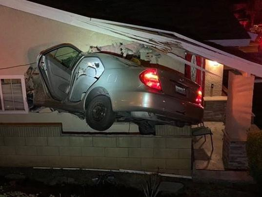 Speeding car filmed flying from road and crashing into side of family home in California thumbnail