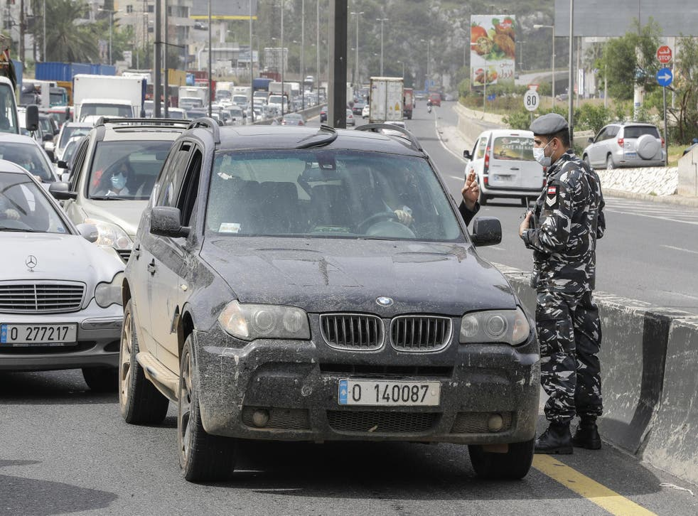 Lebanese security forces stop vehicles at a highway checkpoint near Beirut as part of coronavirus lockdown measures