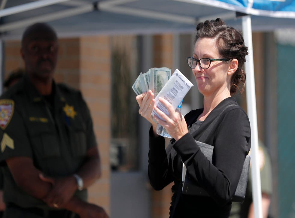 Shaye Spell, wife of Lousiana pastor Tony Spell, flashes wads of cash as she arrives at the East Baton Rouge parish jail to post bond for him following his arrest for flouting coronavirus lockdown orders