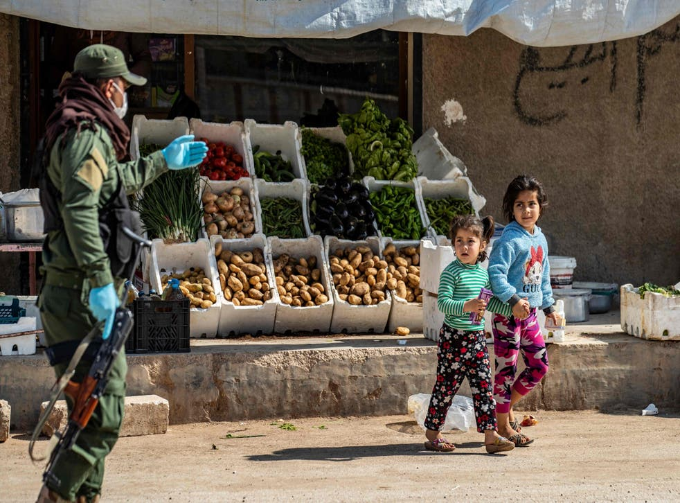 A member of the Kurdish Internal Security Forces urges children to return home in Syria's northeastern city of Hasakeh on Thursday 30 April
