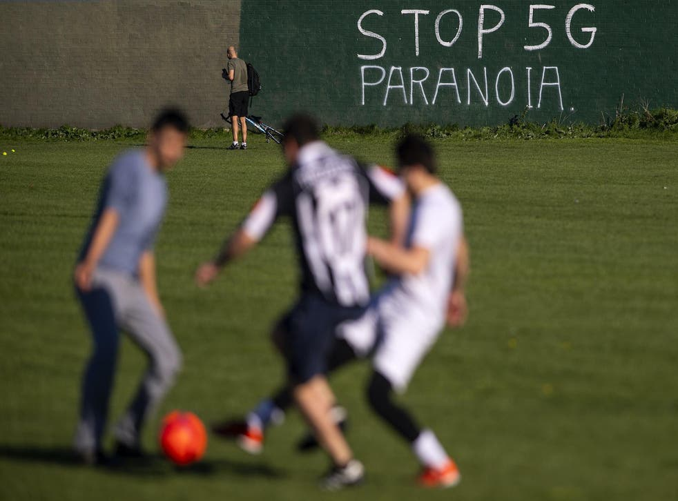 People play football in front of graffiti reading 'Stop 5G Paranoia' painted on a wall in east London on 19 April 2020