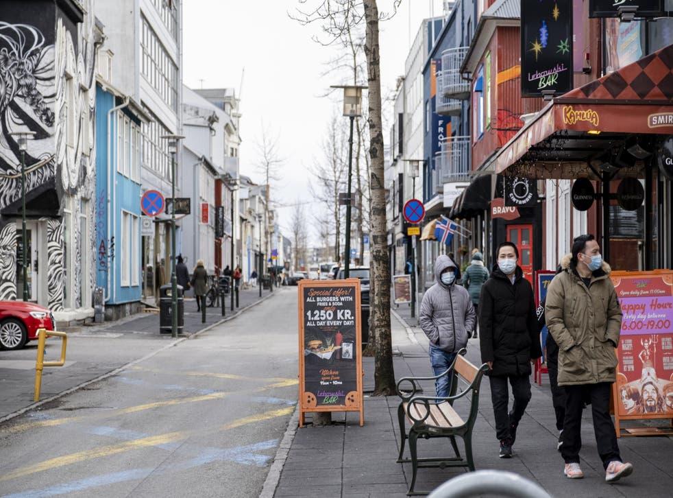 Tourists with masks walk down Laugavegur street in downtown Reykjavik