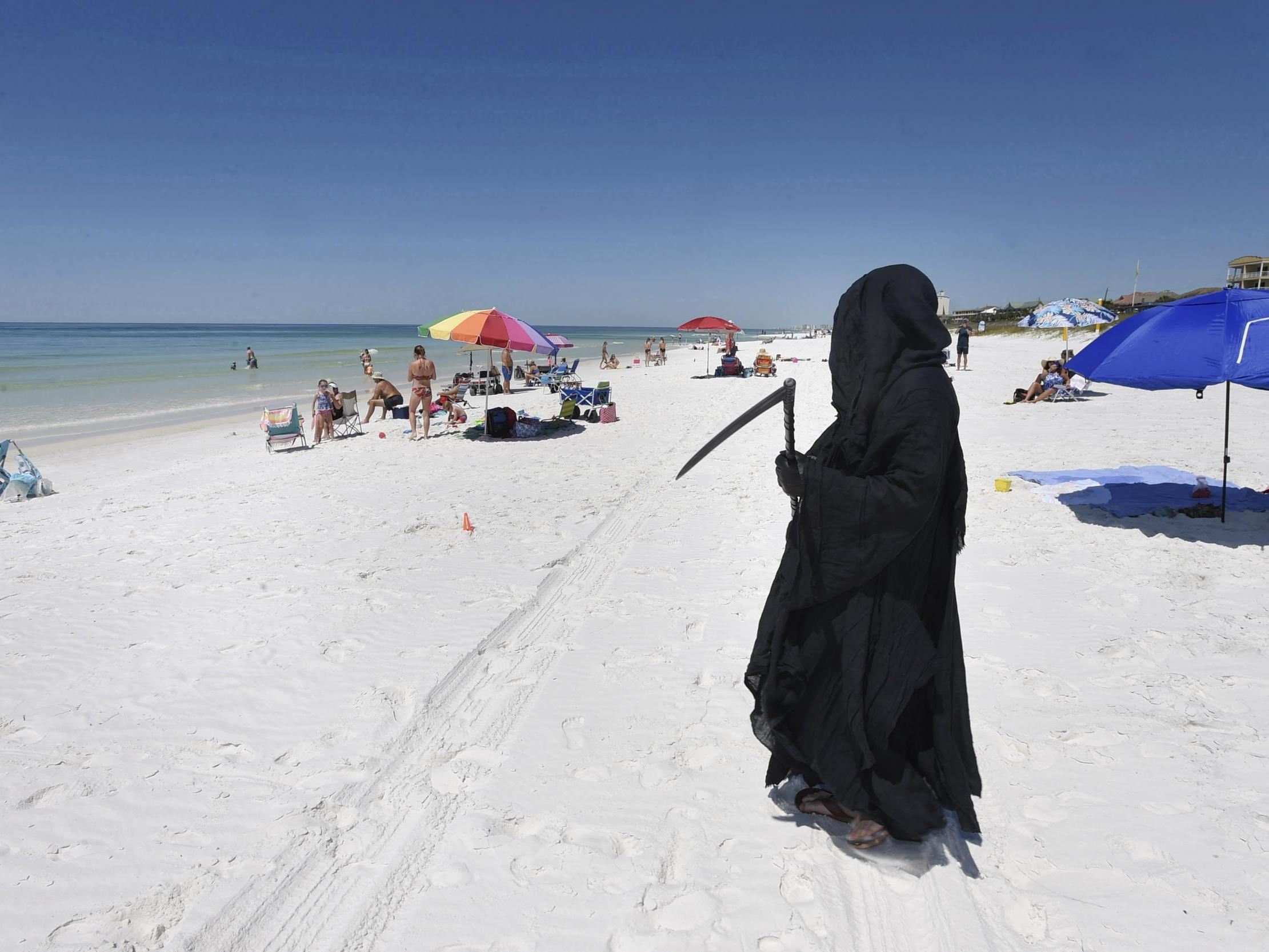 Lawyer dressed as Grim Reaper stalks Florida beaches to protest reopening photo