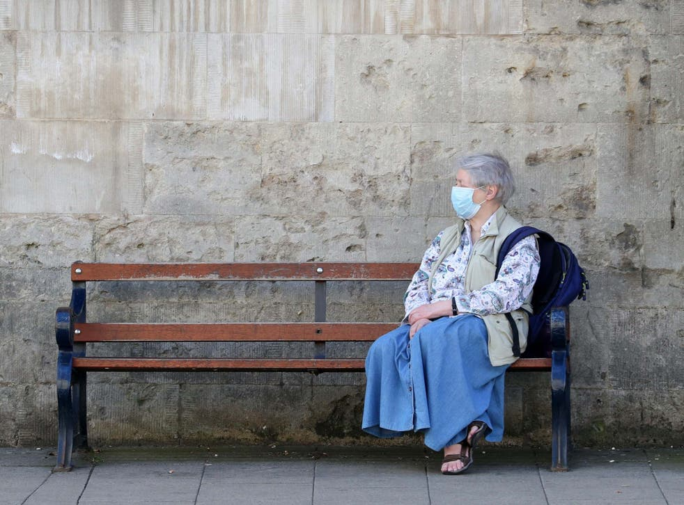 A member of the public wears a face mask as she sits on a bench