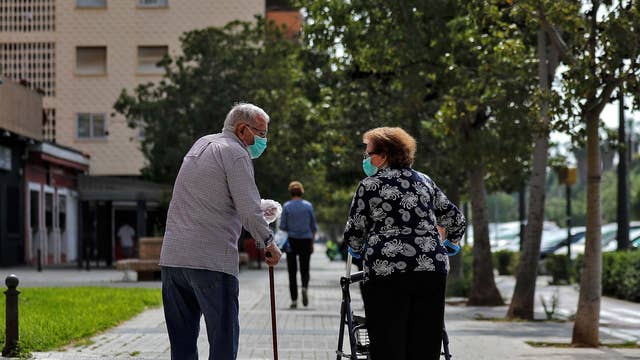 Two elderly people chat on a street in Valencia, Spain on 4 May