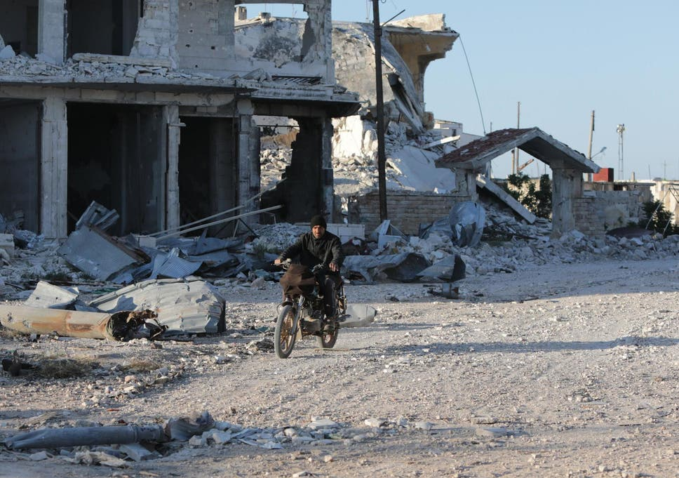 A Syrian man rides his motorcycle in a town ravaged by attacks from pro-Assad forces in Idlib province