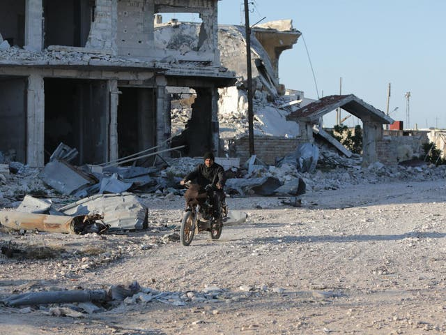 A Syrian man rides his motorcycle in a town ravaged by attacks from pro-government forces in Idlib province