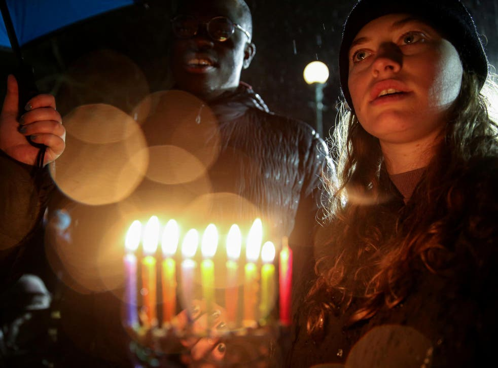 A woman holds candles while standing in solidarity with the victims after an assailant stabbed five people attending a party at an Hasidic rabbi's home in Monsey, New York
