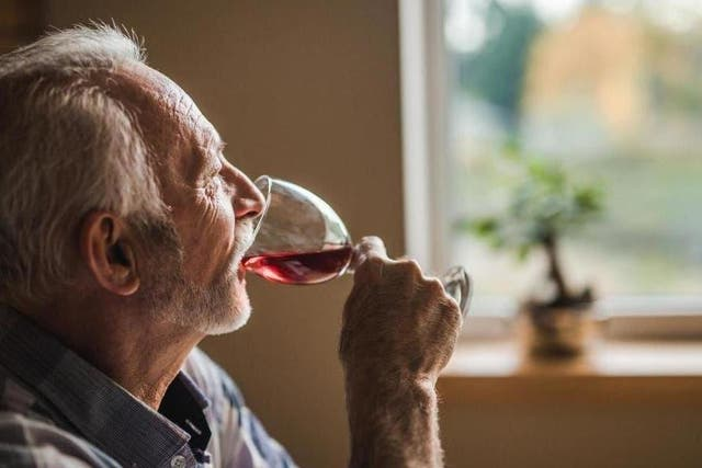 A man drinks red wine at home while looking out of the window