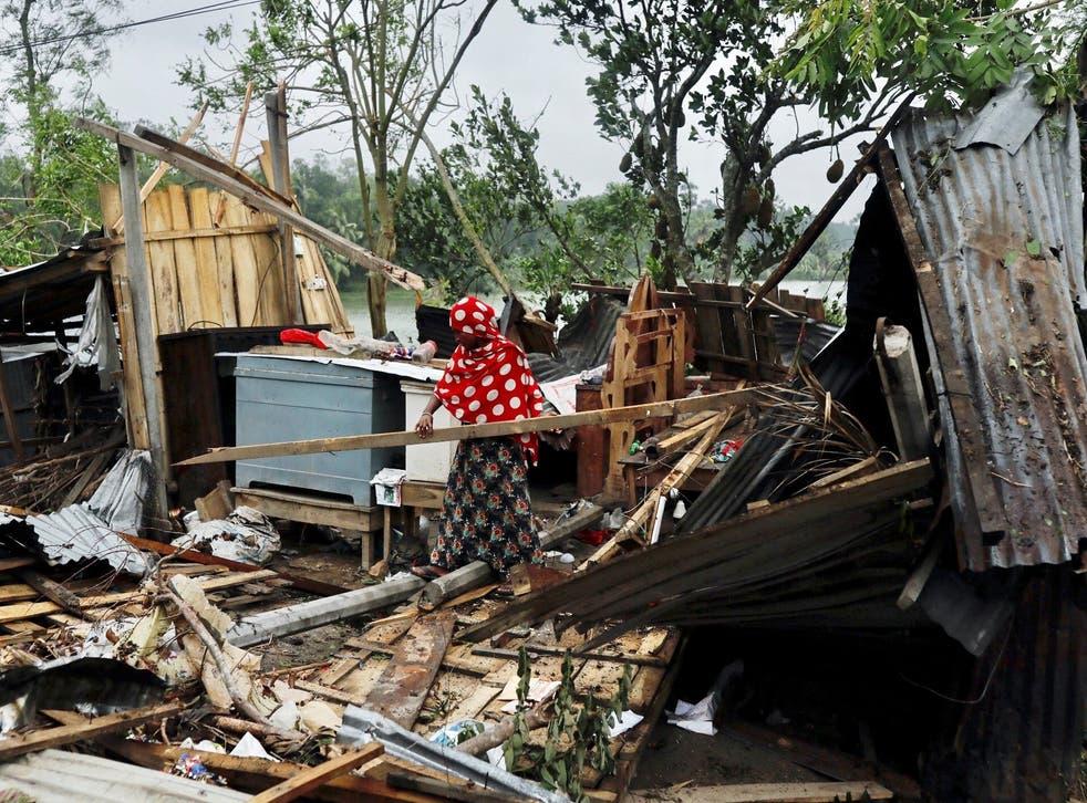Una mujer limpia su casa que fue demolida por el ciclón Amphan en Satkhira, Bangladesh