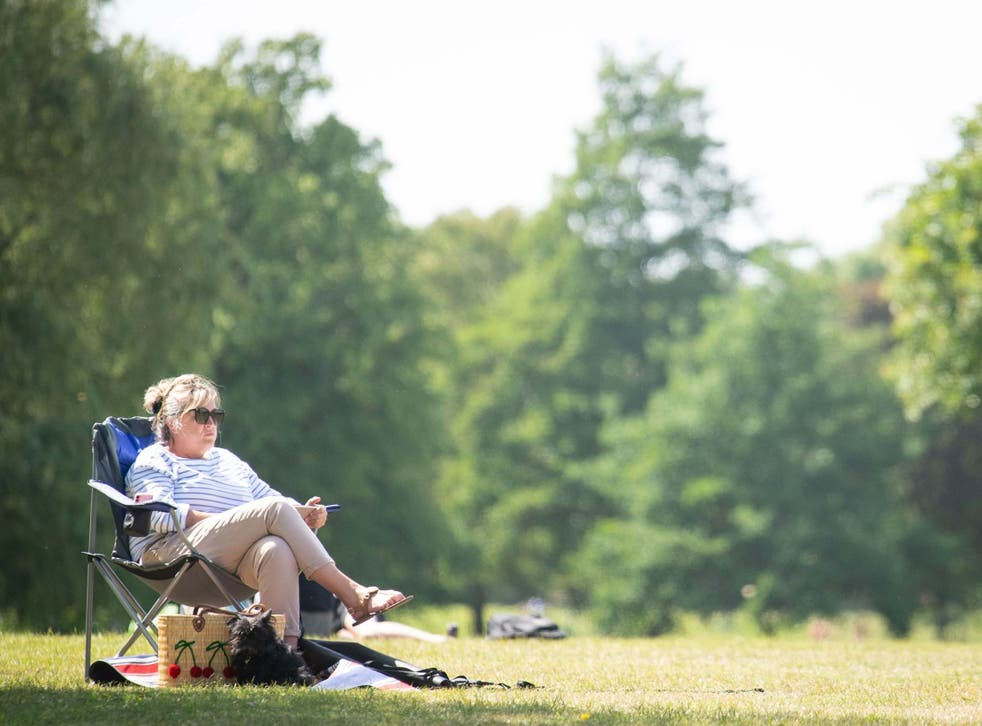 A woman relaxes in the hot weather on Clapham Common