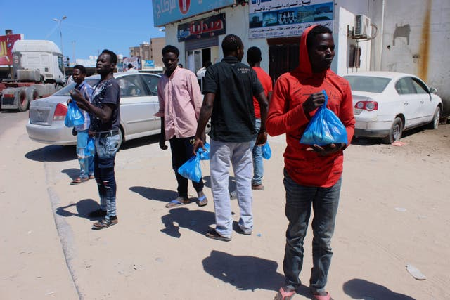 Migrants wait for food handouts in Misrata, Libya