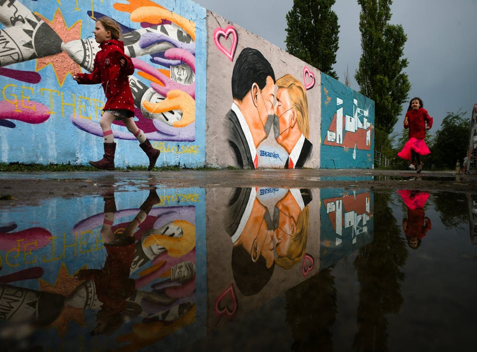 Graffiti of presidents Trump and Xi Jinping kissing each other through face masks on a wall in Berlin's Mauerpark