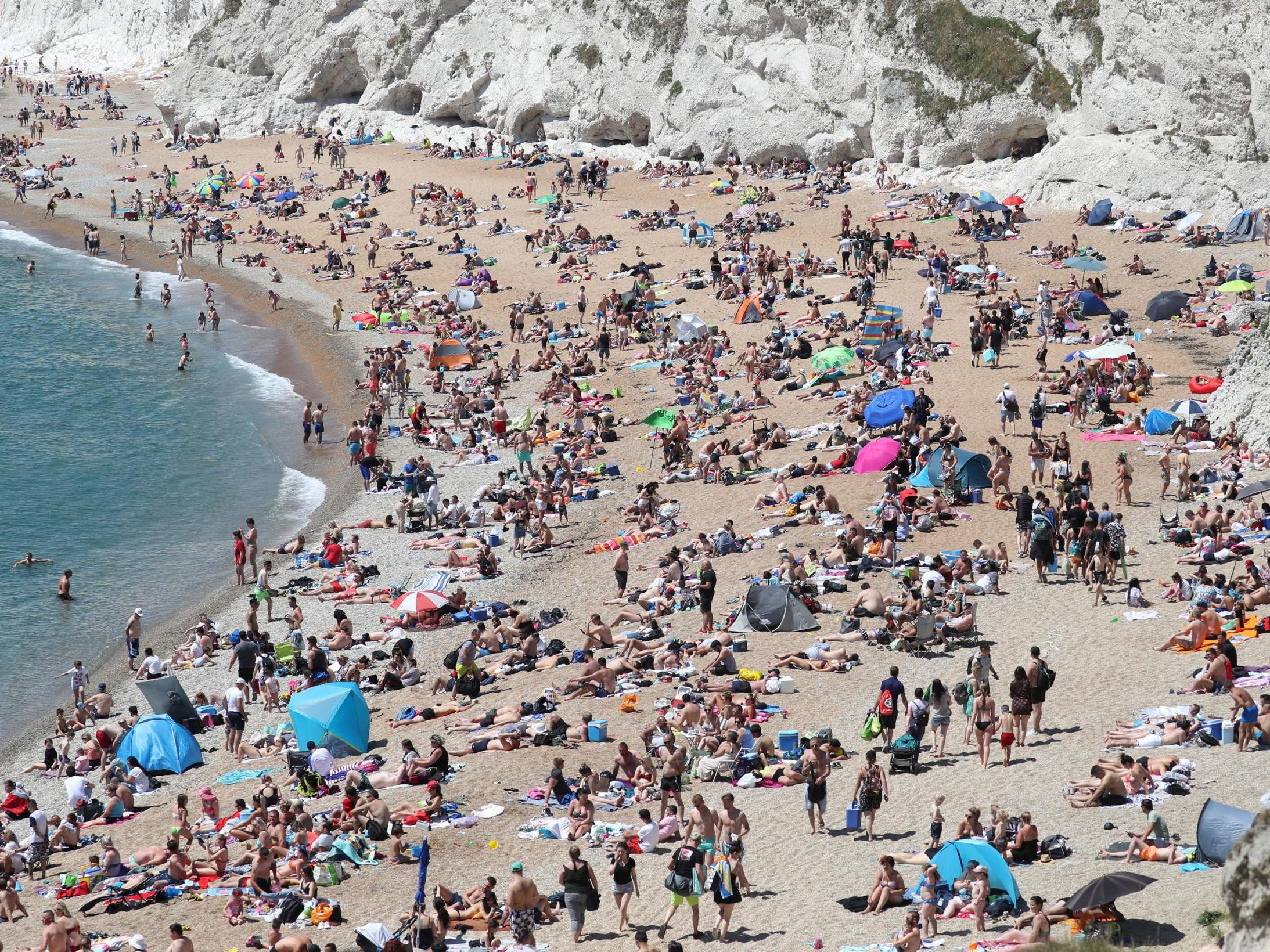 Hundreds ignore police warnings and flock to beach at Durdle Door after serious cliff injuries