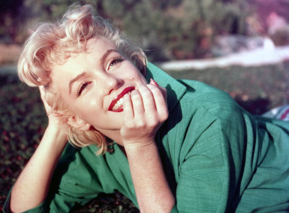 Marilyn Monroe poses for a portrait laying on the grass in 1954 in Palm Springs, California
