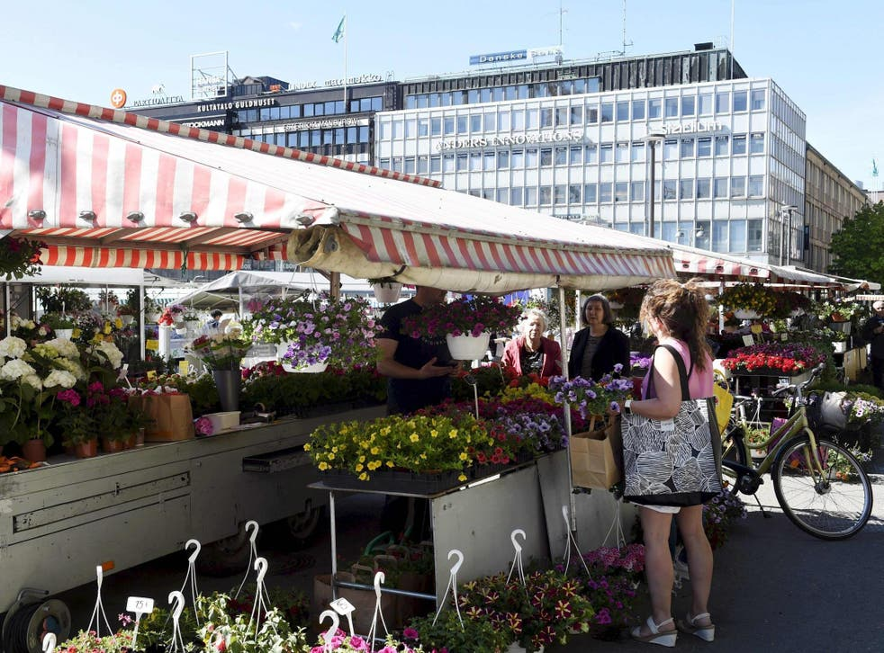 A woman buys flowers at the market square in Turku, Finland, 28 May