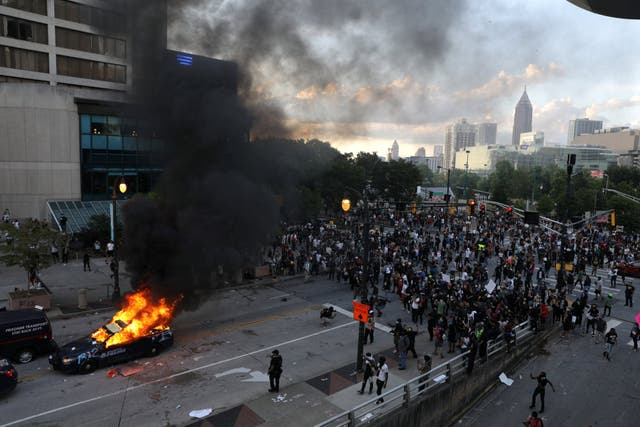 A police car burns in Atlanta during a protest over the death of George Floyd