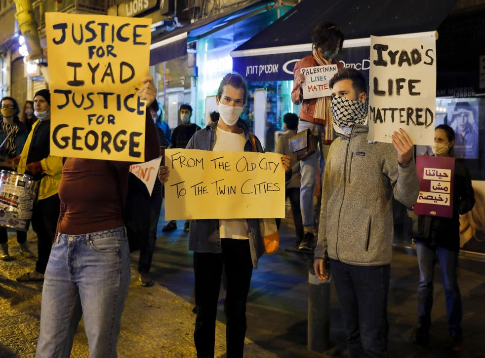 Israeli demonstrators carry placards during a demonstration condemning the shooting of Iyad Hallak, a disabled Palestinian man who was shot dead by Israeli police