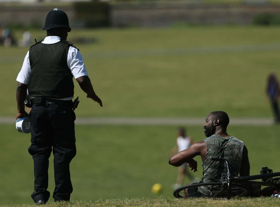 A police officer moves sunbathers in Greenwich Park, London, on 9 May