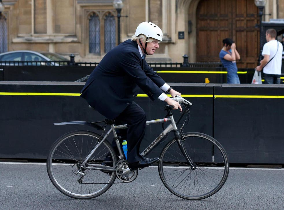 Boris Johnson cycles past the Houses of Parliament in 2013 during his second term as mayor of London