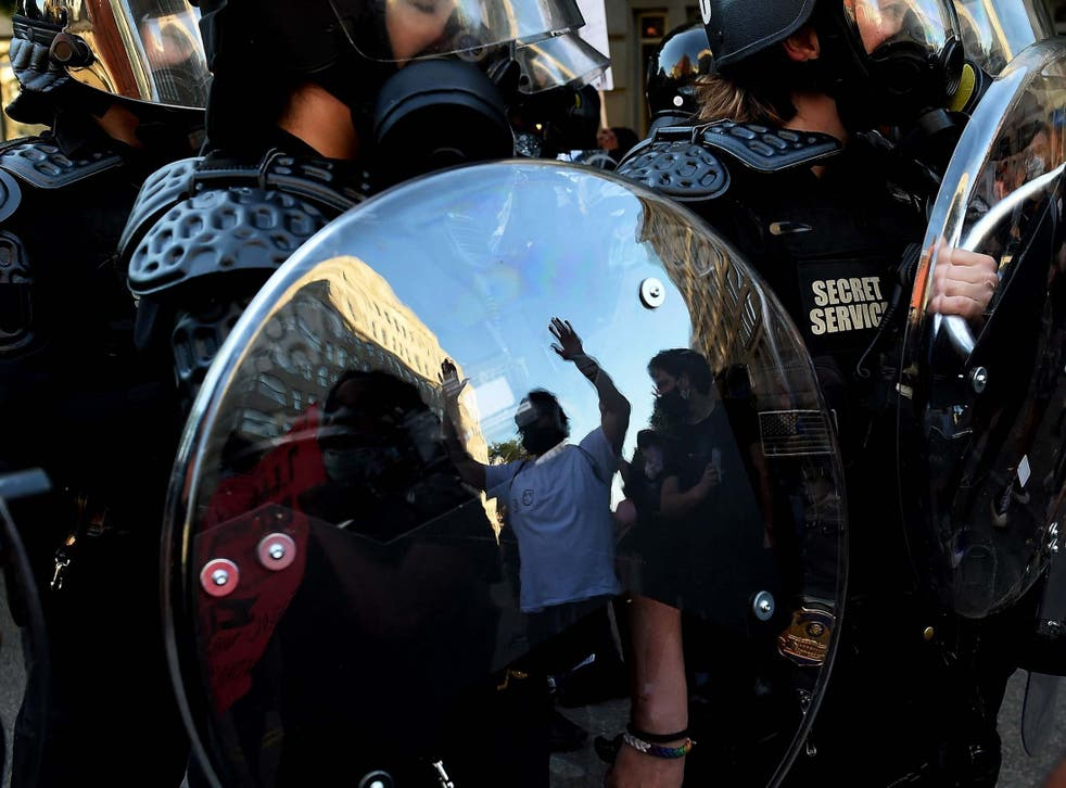 A protester is reflected in the shield of police officers during a demonstration against the death of George Floyd