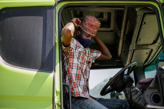 Tanzanian truck driver Ally Akida Samwel fixes his mask to curb the spread of the coronavirus, a legal requirement for anyone in public in Kenya, as he prepares to enter on the Kenya side of the Namanga border crossing with Tanzania
