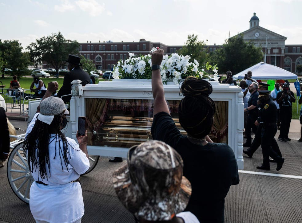 Mourners watch as the casket of George Floyd is carried by a white horse-drawn carriage to his final resting place at the Houston Memorial Gardens cemetery in Pearland, Texas on June 9, 2020.