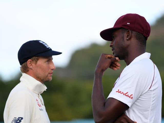 England captain Joe Root (left) talks with West Indies captain Jason Holder