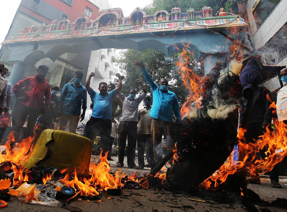 Activists burn photos of Chinese President Xi Jinping during a protest in Bangalore