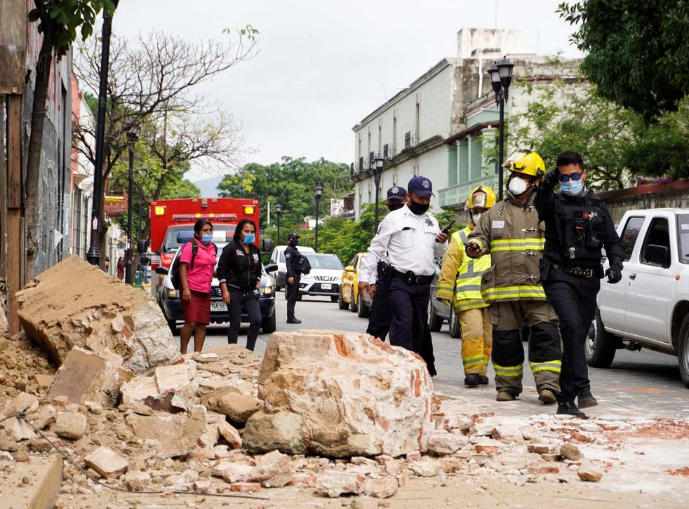 Members of the police and fire department observe the damage caused by a collapsed wall in Oaxaca, Mexico, 23 June 2020