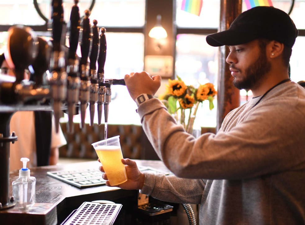 A bartender pours pints for takeaway customers at The Ten Bells pub in east London on June 27, 2020.