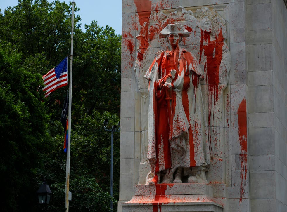 A statue of former US President George Washington is covered in red paint after being vandalised in Washington Square Park in New York