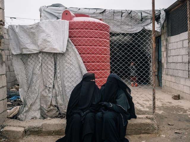 Russian women sit outside a shop in the foreigner's section of al-Hol camp in December 2019