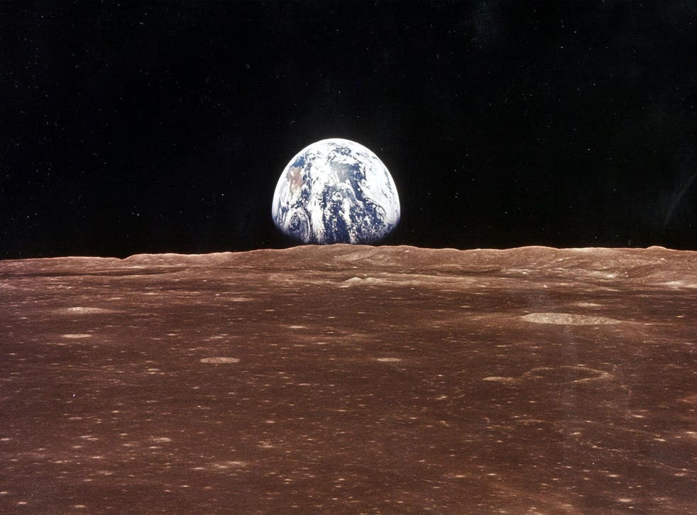 A view of the Earth appears over the Lunar horizon as the Apollo 11 Command Module comes into view of the Moon