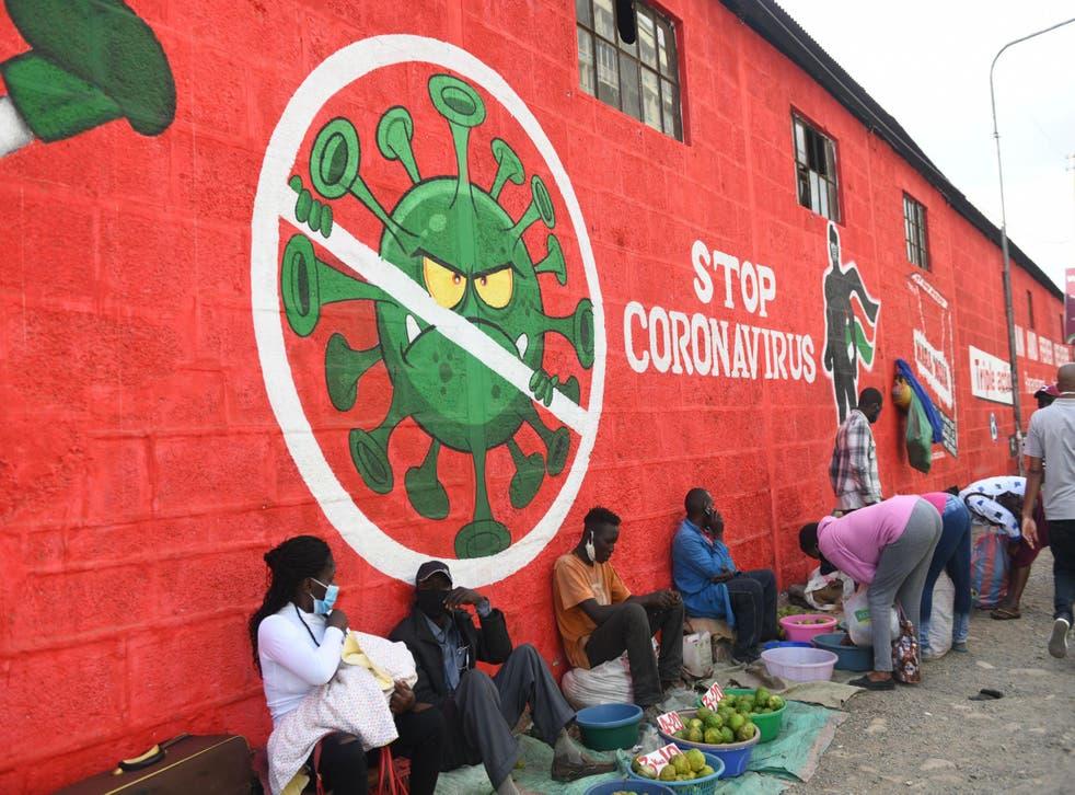 Traders sell their wares below graffiti raising awareness about Covid-19 in Nairobi last month