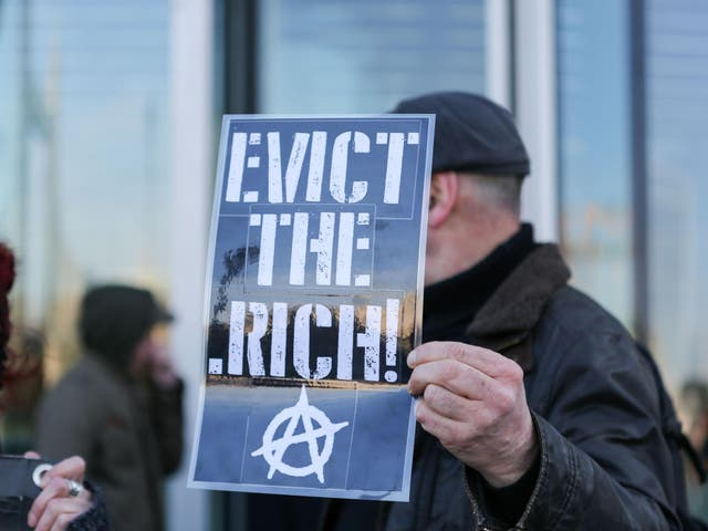 An anarchist holds aloft a placard at an anti-gentrification protest in London in 2018