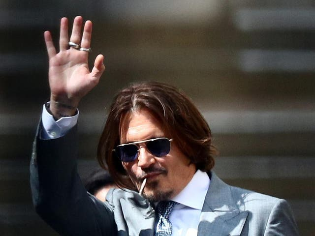 Johnny Depp waves as he leaves the High Court in London