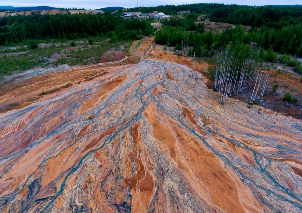 Orange-coloured rivers fan out over forested landscape near village of Lyovikha in the Urals