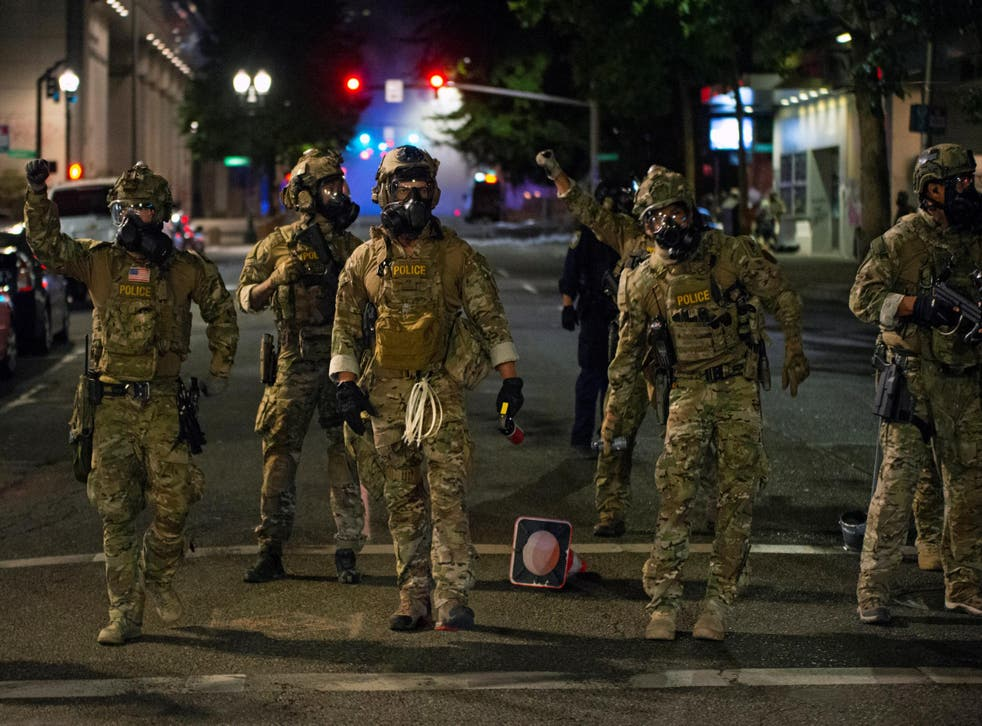 Federal law enforcement officers, deployed under the Trump administration's new executive order to protect federal monuments and buildings, face off with protesters against racial inequality in Portland, Oregon, U.S. July 18, 2020.
