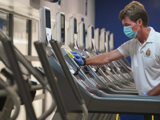 David Silver, a fitness and rehab instructor, cleans down gym machines at the North Tyneside Council Waves Gym