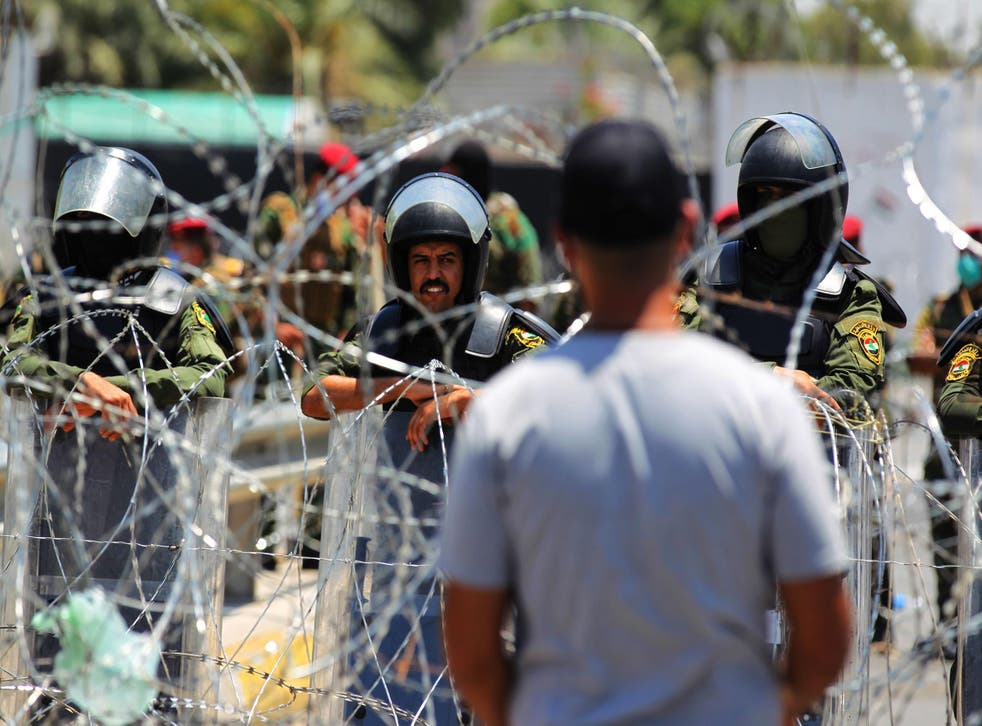 Iraqi security forces stand guard outside the entrance of the Green Zone during a protest in the capital Baghdad in July