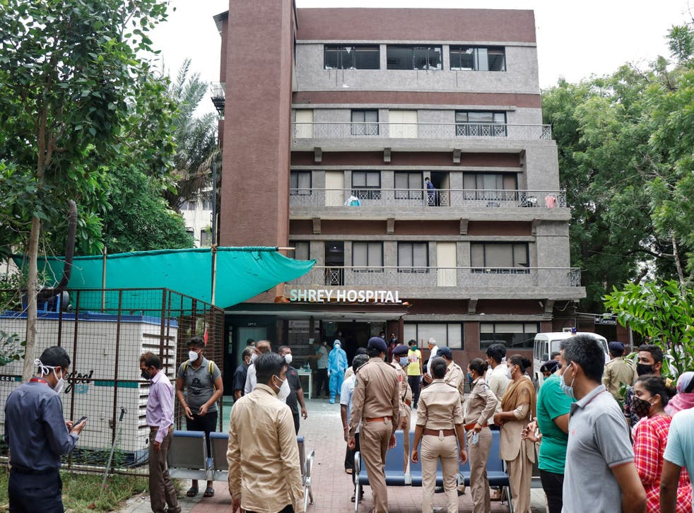 Police officers and relatives outside a hospital where a fire broke out on Thursday in Ahmedabad, India, killing eight Covid-19 patients