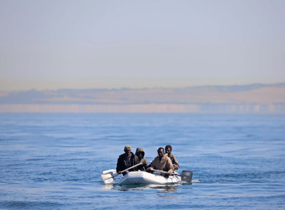 Four men off the coast of France, some using shovels as paddles, use a small dinghy to cross the English Channel on 7 August 2020