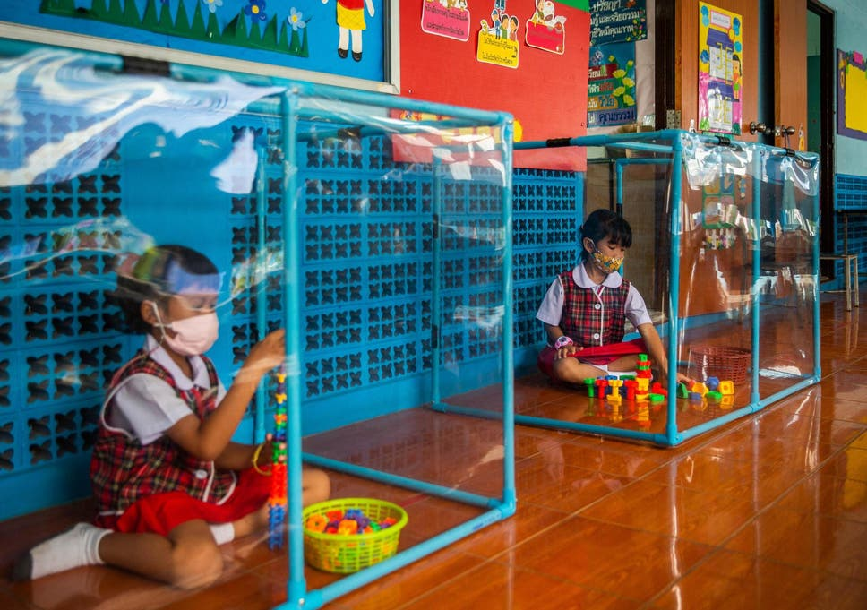 Two Thai pupils play behind plastic screens in separate play areas at the Wat Khlong Toey School on August 10, 2020 in Bangkok, Thailand.