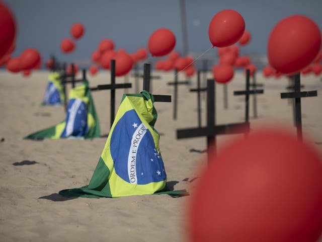 Crosses, red balloons and Brazilian nation flags are placed in the sand on Copacabana beach in a demonstration organised by Rio de Paz