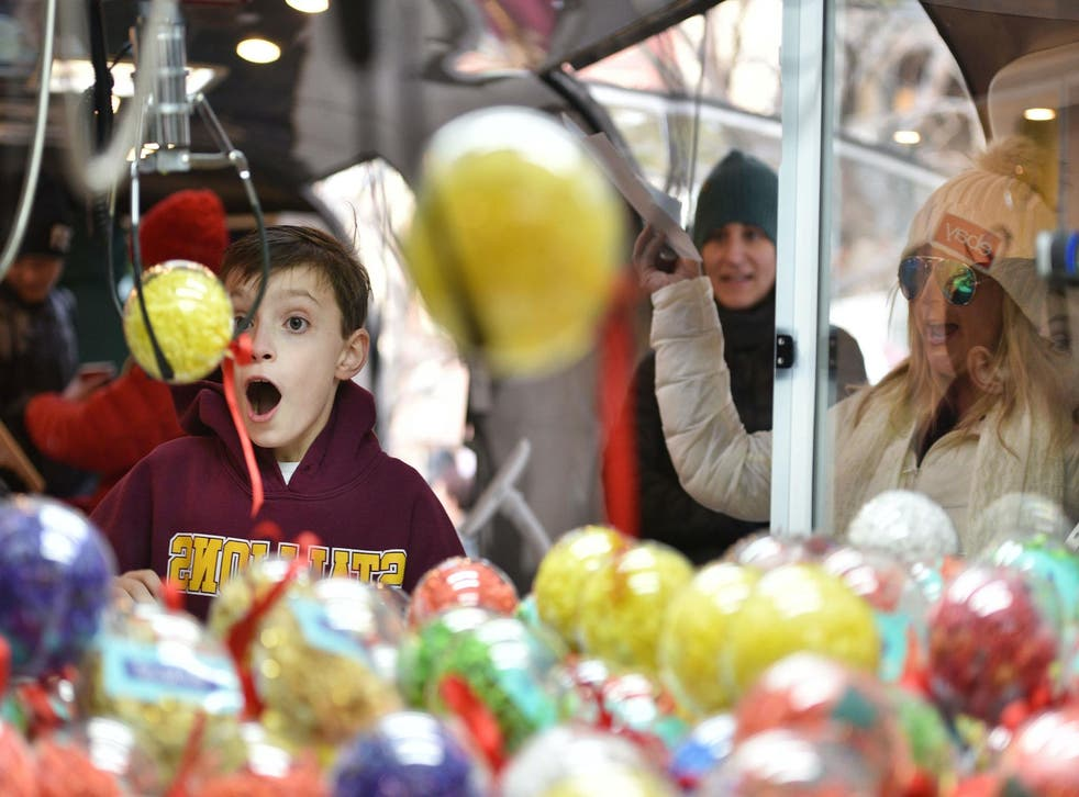 Aden Foster of Colorado Springs wins a prize on the ebay claw machine as Codie Murphy cheers him on at the 'Did You Check eBay?' Holiday Airstream at Christkindl Market on December 4, 2017 in Denver, Colorado
