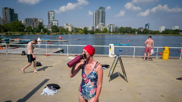 A woman hydrates in the sun after open water swimming at the West Reservoir Centre in north London