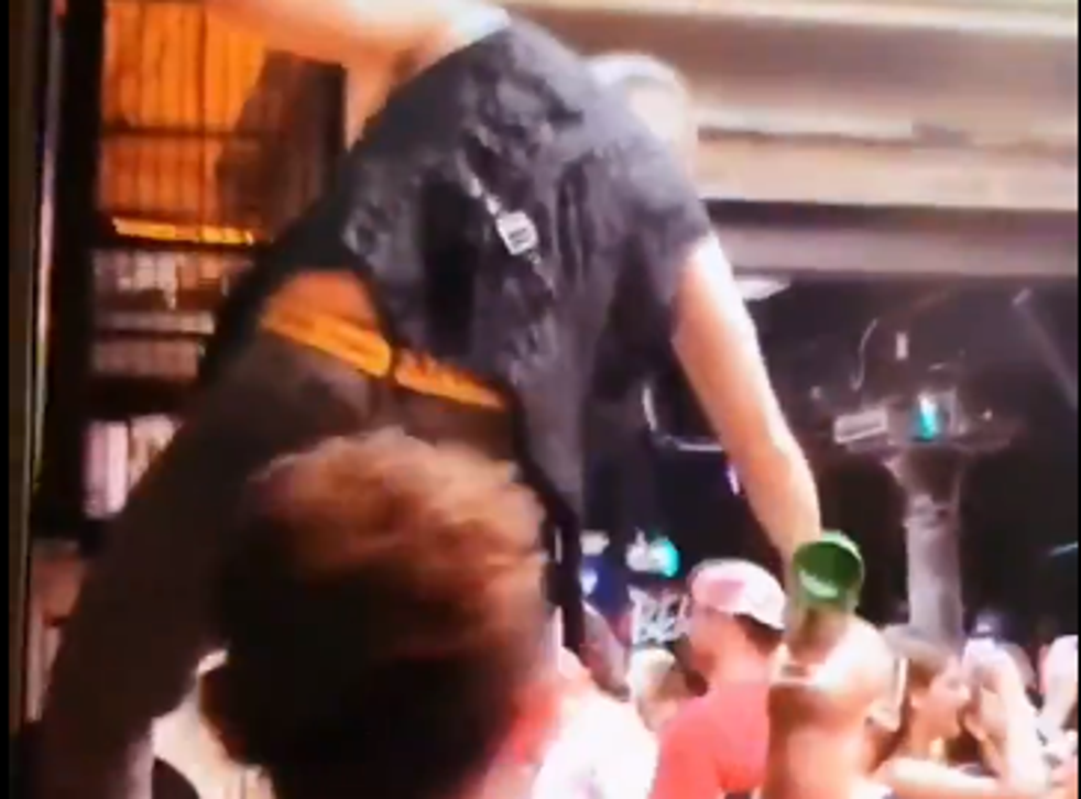 A man standing on the bar pours drinks directly into customer's mouths during the party